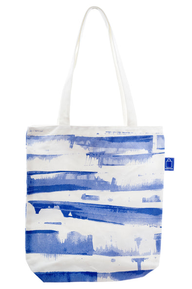 A versatile cotton tote with blue and white design. It has a zip for closure and a small inside pocket. Large enough to hold an ipad, laptop or some groceries.