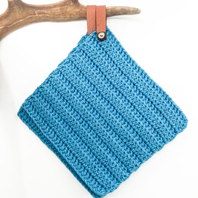 Handmade potholder in turquoise cotton. The loop is made of reindeer leather with a reindeer antler button, and the loop can be taken off if needed. julevu sweden