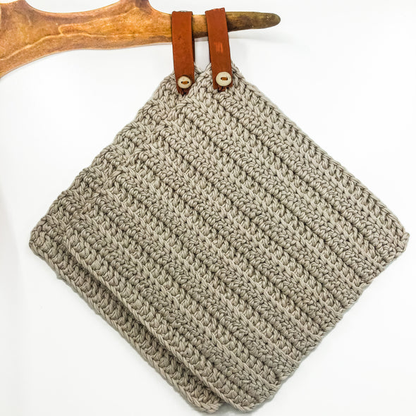 Handmade potholder in beige cotton. The loop is made of reindeer leather with a reindeer antler button, and the loop can be taken off if needed. Julevu Sweden