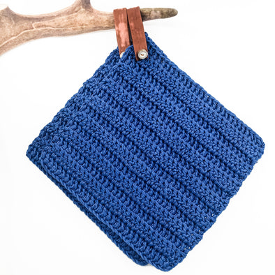 Handmade potholder in blue cotton. The loop is made of reindeer leather with a reindeer antler button, and the loop can be taken off if needed.