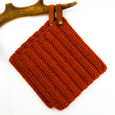 Handmade potholder in rust cotton. The loop is made of reindeer leather with a reindeer antler button, and the loop can be taken off if needed.