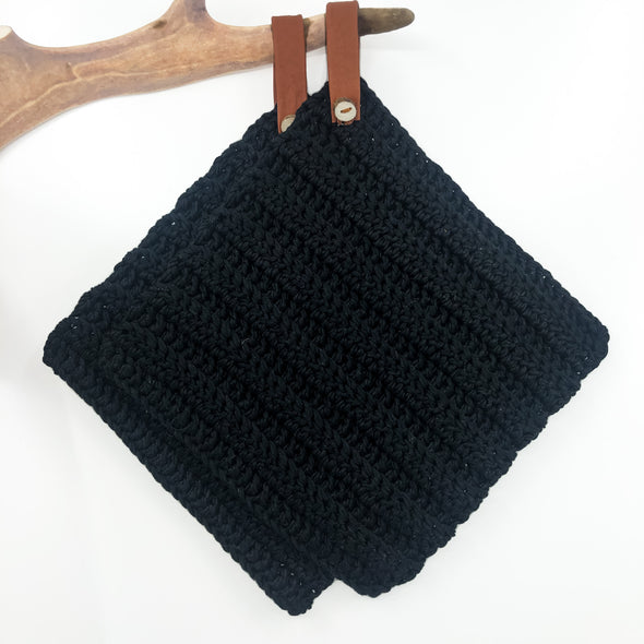 Handmade potholder in black cotton. The loop is made of reindeer leather with a reindeer antler button, and the loop can be taken off if needed. julevu.com