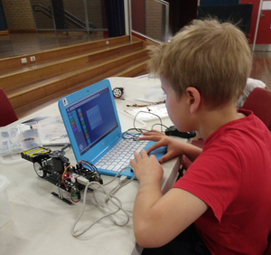 A boy is coding a robot in RUNSTEM Robotics Class in Sydney