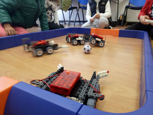 Robots fight for the ball at the soccer robotics school holidays camp