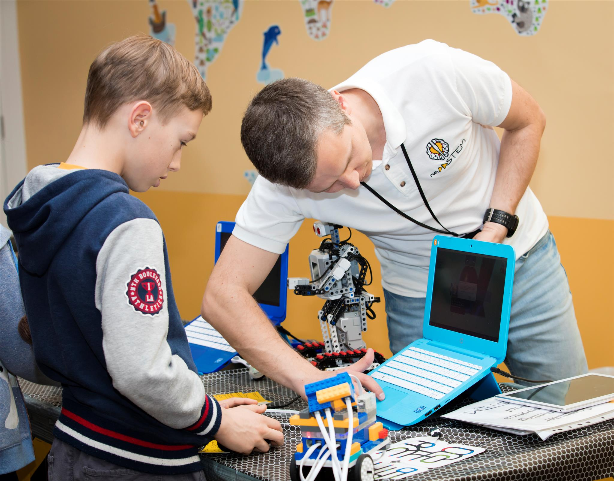 RUNSTEM Educator explains to a student how to code a game and shows some robots