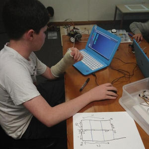 A boy is coding his robot to complete a programming challenge