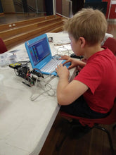 A boy learns how to code a robot