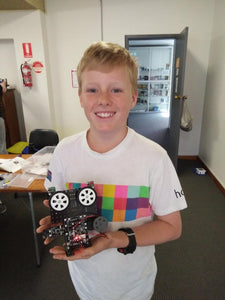 A boy shows his robot at RUNSTEM robotics school