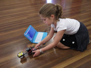 A girl is adjusting her robot and coding robot to complete a challenge