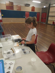 A girl is building a robot at robotics class