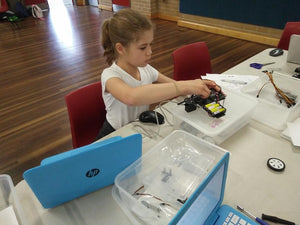 A girl is finishing her robot project