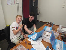 Boys are happy to finish coding a robot at robotics class