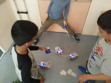Boys are testing their programmable robots during robotics class