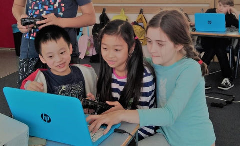 Girls are showing a boy a game they have finished coding over a day camp at RUNSTEM coring and robotics STEM school