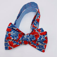 self-tie bow tie in Liberty London Tana Lawn pima cotton with adjustable neck strap for perfect fit.  Red poppy with blue florals in background.  A gatsby, deco vibe.