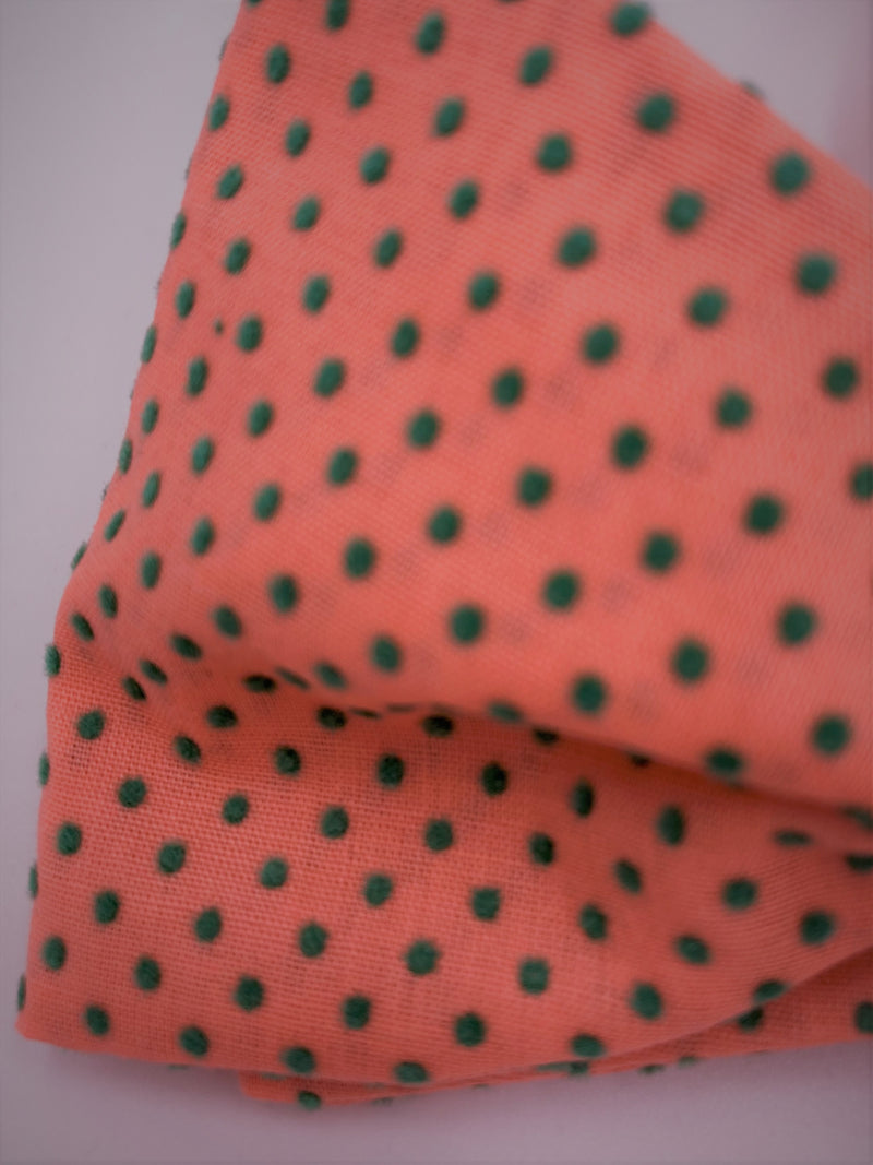Swatch of vintage flocked swiss dot in lovely peach color with muted green dots