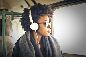 beautiful black women with headphones looking out window