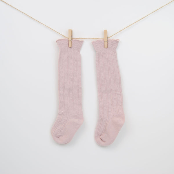 Knee-high cable knit patterned cuff socks in crepe pink.