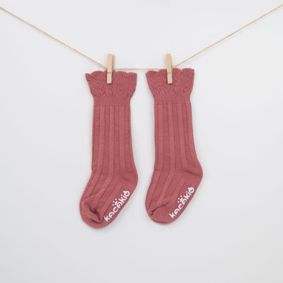 Tall cable knit patterned cuff socks in dark pink.