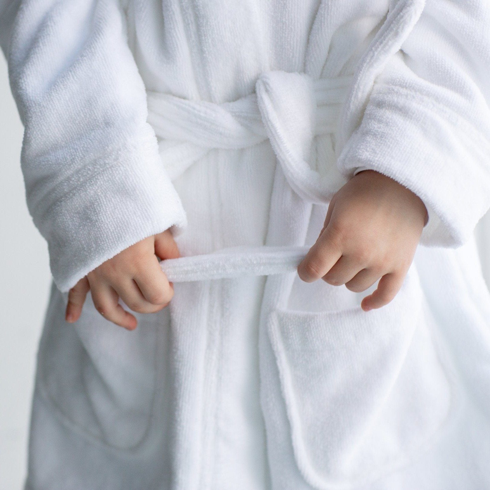 Close up child hands and bathrobe