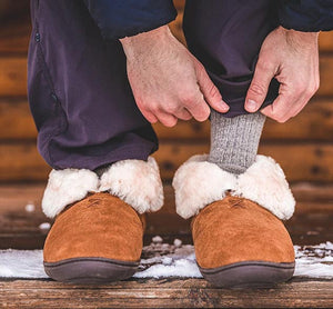 Man shows off gray socks and Staheekum Tundra Slipper Booties for men with folded cuff.
