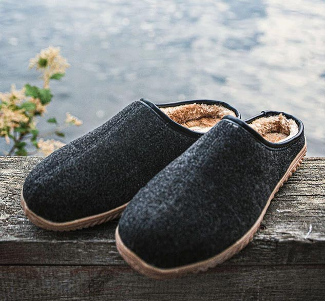 Staheekum Wallace men's slip-on slippers in gray seated on a wooden rail by a lake.