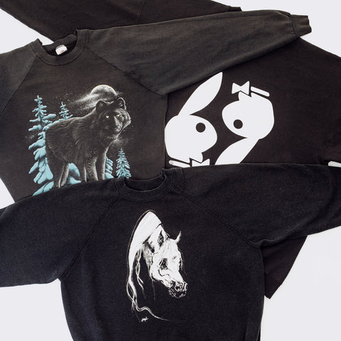 Three vintage graphic sweatshirts laid flat. All three are black. One has a image of a horse, one has a pack of wolves, and the last one has the playboy bunny logo.