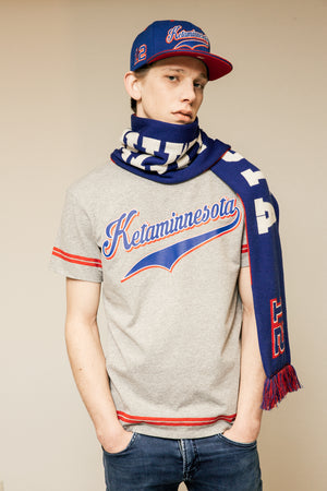 man wearing a cap a t-shirt and a scarf with a giant ketaminnesota writting made in italy. model in the lookbook of spleen unconventional