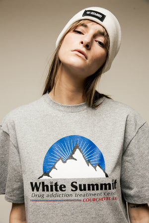 model wearing a grey t-shirt with a giant print on chest of a white mountain with a white summit writting stating drug addiction treatment center Courchevel 1850