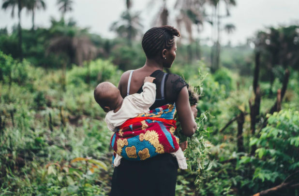 Mummy in a field with baby tied to her back with traditional african cloth