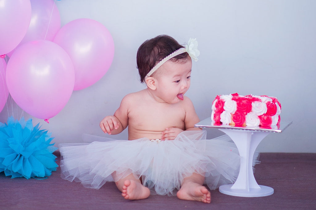 Baby girl sitting in tutu, staring at pink and white birthday cake