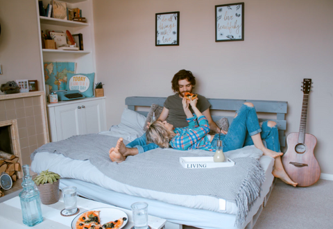 Couple on bed, woman feeding her boyfriend