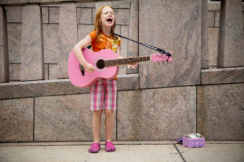Little girl singing busking with pink guitar