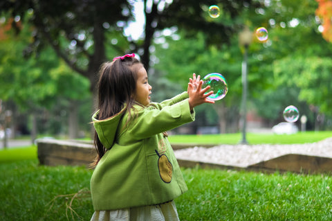 Little girl in the park playing with bubble