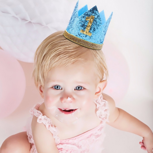 Young child wearing glittery blue birthday number 1 crown