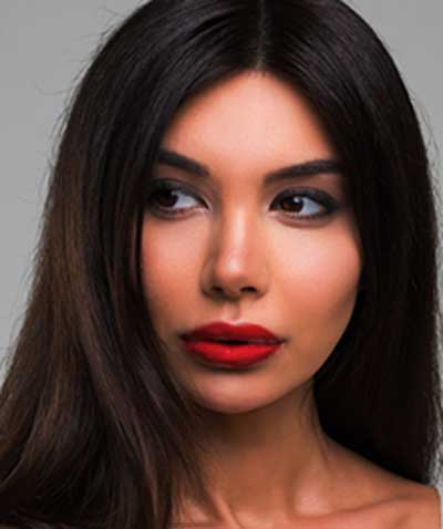 Latina woman wearing Argentine Red Tango lipstick by Plum & York