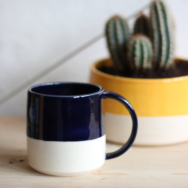 Examples of colours that are available for FICH mugs. The mug in this photo is Navy Blue.