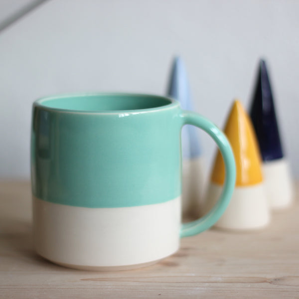 In this photo there is a mug in Jade Green which is one of the colour options available in FICH mugs.