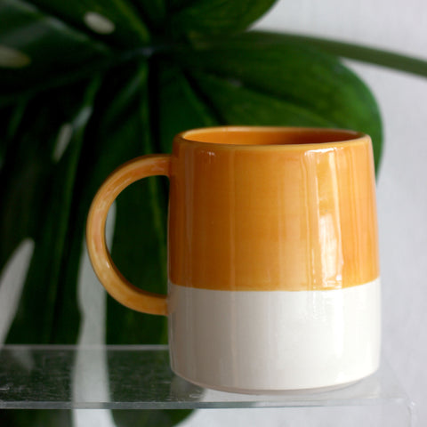 In this photo there is a mug in Mustard Yellow which is one of the colour options available in FICH mugs.