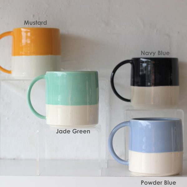 Examples of colours that are available for FICH mugs. The colours being shown are Mustard, Jade Green, Navy Blue and Powder Blue.