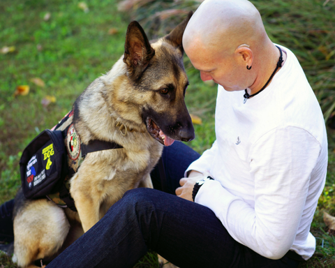 Young mand and service dog well trained dog sitting quietly