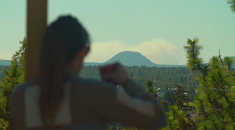 Woman stares at Pilot Butte from distance in Bend, Oregon