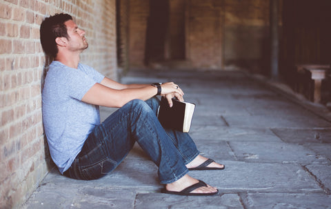 Man meditating against brick wall with book in hand