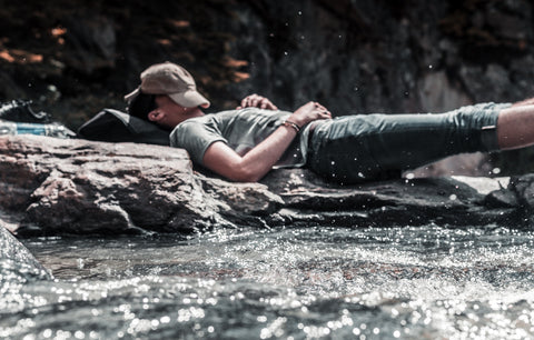 Man sleeping by river with hat covering face