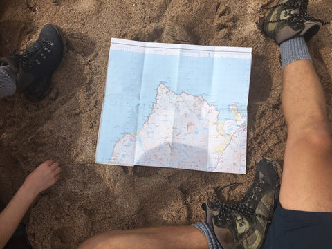 Sitting on beach reading map, photo by Paul Hughes