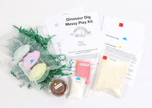 Materials and contents of Dinosaur Dig Messy Play Kit including instructions, dinosaur eggs, play dough, volcano mix, citric acid, and fossil mix.