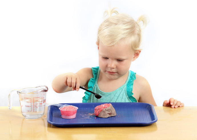 Girl concentrating on using a teaspoon to pour liquid over a clay volcano making it erupt with red lava.