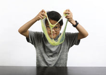 Load image into Gallery viewer, Young boy wearing glasses stretching green and yellow color-changing Caterpillar slime in front of his face.