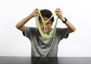 Young boy wearing glasses stretching green and yellow color-changing Caterpillar slime in front of his face.