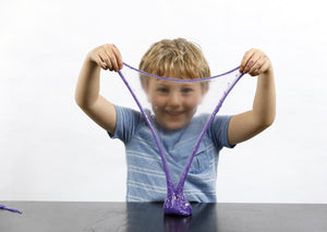 Young boy stretching purple Rockstar slime in front of his face.
